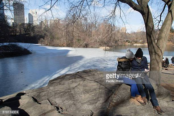 A couple sit in front of a frozen lake in Central Park Mayor De Blasio tells New Yorkers to stay indoors as temperatures continue to drop and New...