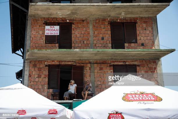 A couple sit on a balcony above beer tents in the town during the Guca Trumpet Festival on August 12 2017 in Guca Serbia Thousands of revellers...