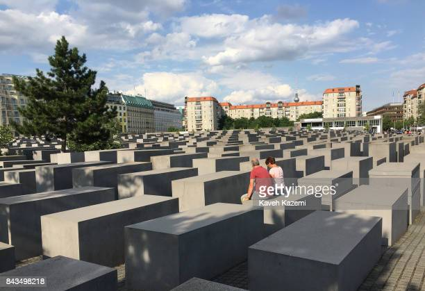 A couple sit on a concrete slabs or 'stelae' in The Memorial to the Murdered Jews of Europe also known as the Holocaust Memorial designed by...