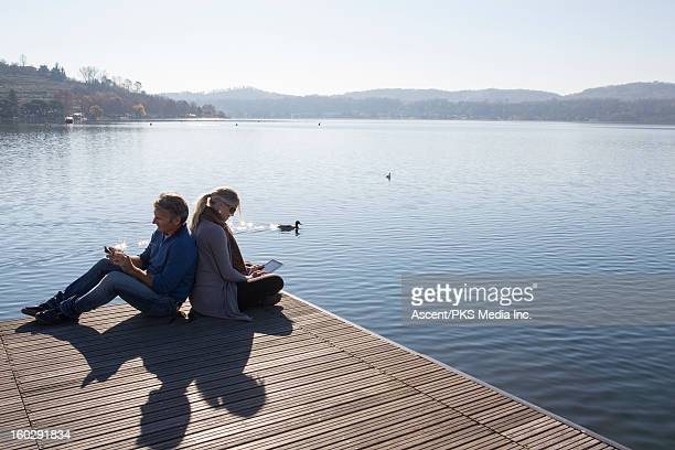 Couple sit on dock abovve lake,use tablet and cell