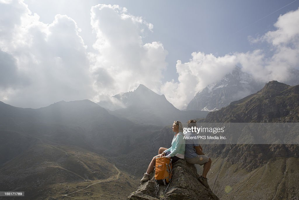 Couple sit on pinnacle summit, look off to mtns : Stock Photo