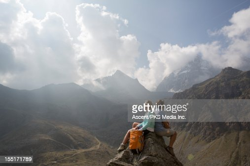 Couple sit on pinnacle summit, look off to mtns : Foto de stock
