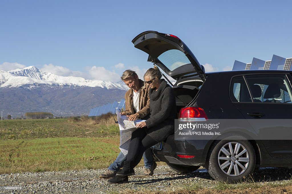 Couple sit on tail of car with map, solar facility : Stock Photo