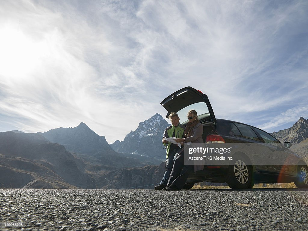 Couple sit on tailgate of car, look at map, mtns : Stock Photo