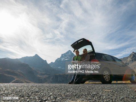 Couple sit on tailgate of car, look at map, mtns : Foto de stock