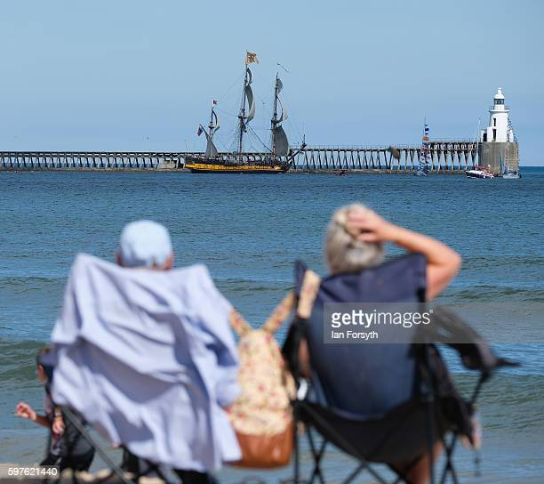 A couple sit on the beach and watch as the Russian ship Shtandart leaves Blyth harbour during the North Sea Tall Ships Parade of Sail on August 29...