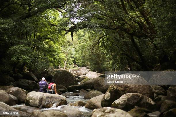 A couple sit on the rocks of the Mossman river in world heritage listed daintree rainforest on November 15 2012 in Mossman Gorge Australia Located in...