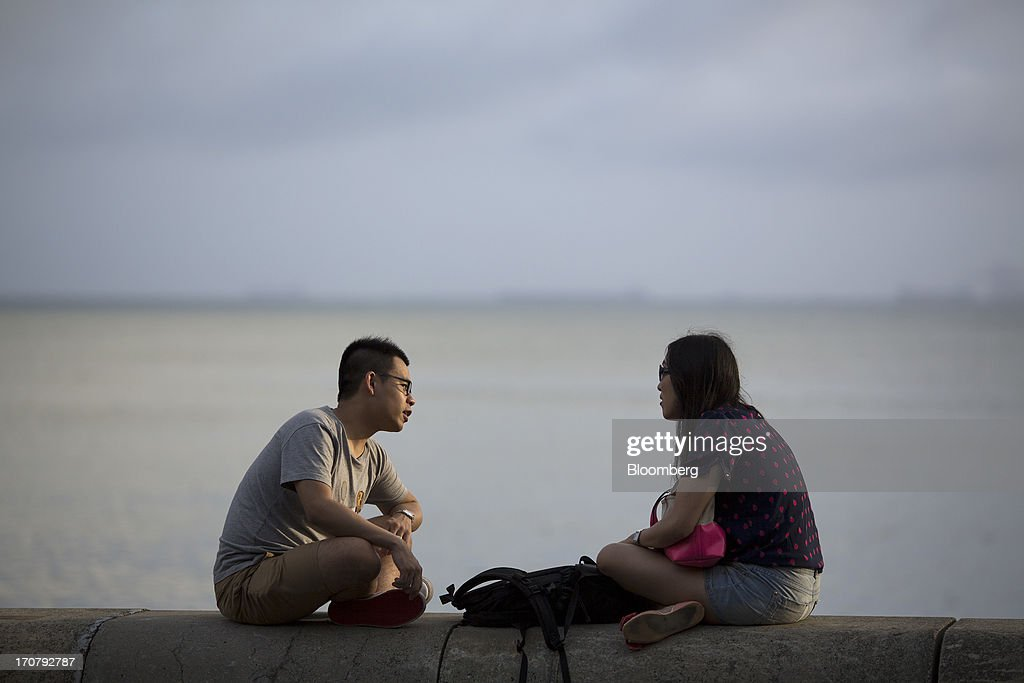 A couple sit on the waterfront in the Stanley area of Hong Kong, China, on Sunday, June 16, 2013. A shortage of housing, low mortgage costs and a buying spree by mainland Chinese have led home prices to more than double since the beginning of 2009, shrugging off repeated attempts by the government to curb gains amid an outcry over affordability. Photographer: Jerome Favre/Bloomberg via Getty Images