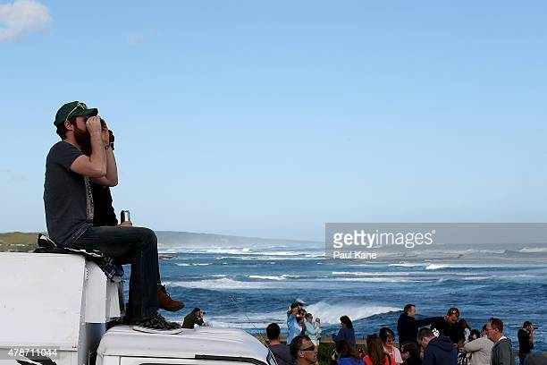 A couple sit on top of their vehicle watching people surfing at Surfers Point on June 27 2015 in Margaret River Australia Monster swells were...