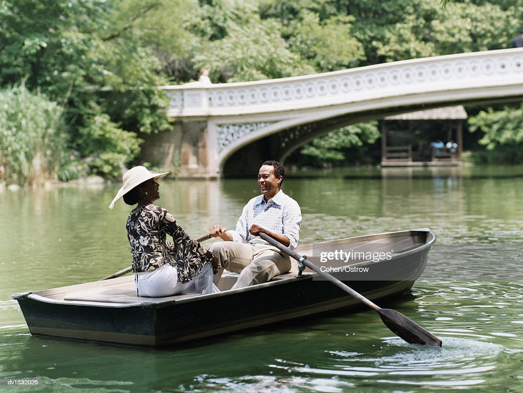 Couple Sit Opposite Each Other in a Rowing Boat on a River in Central Park, Laughing : Stock Photo