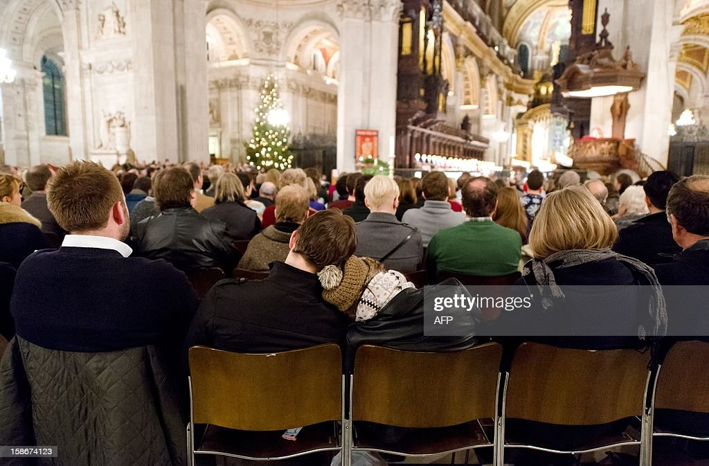 A couple sit together in St Paul's Cathedral in central London during the Christmas carol service on 23 December, 2012. AFP PHOTO/Leon Neal