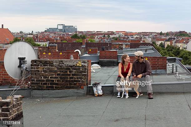 couple sit together with dog on roof, skyline in background