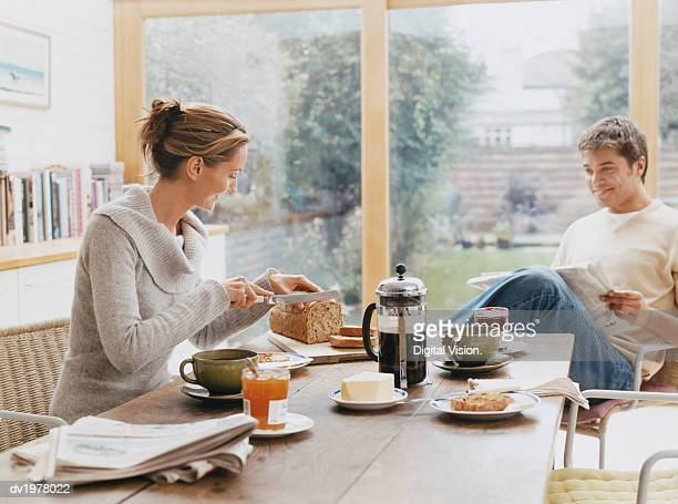 Couple Sits at a Kitchen Table Having Breakfast