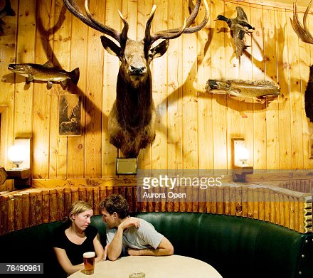 A couple sits in a booth beneath a wall of stuffed wildlife in Wyoming. : Stock Photo
