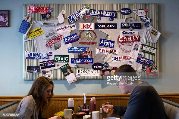 A couple sits in front of a display of political candidate paraphernalia at Chez Vachon restaurant on primary day February 9 in Manchester New...