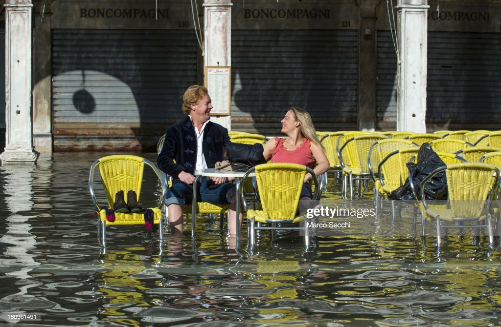 A couple sits in Saint Mark's Square during today's Acqua Alta on November 5, 2013 in Venice, Italy. The high tide, or acqua alta as it is locally known, is a natural event most commonly affecting the city during Autumn and Winter.