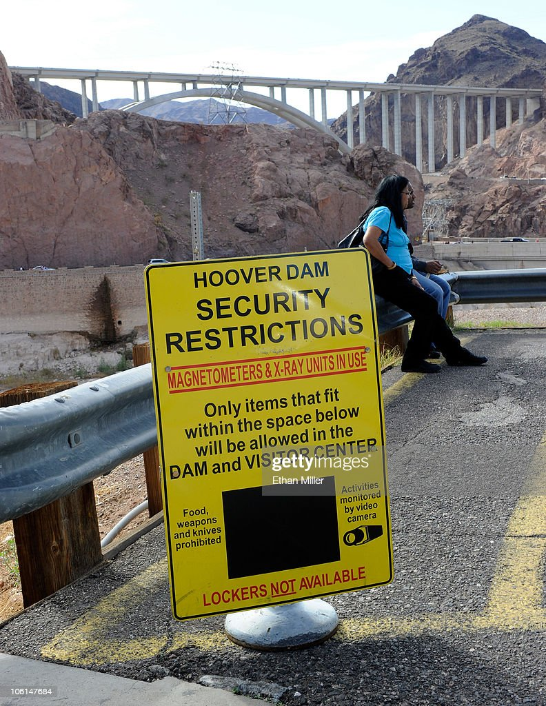 A couple sits near a security sign at the Hoover Dam with the Mike O'Callaghan-Pat Tillman Memorial Bridge part of the Hoover Dam Bypass Project visible October 26, 2010 in the Lake Mead National Recreation Area, Arizona. The 1,900-foot-long structure sits 890 feet above the Colorado River, about a quarter of a mile downstream from the Hoover Dam. The USD 240 million four-lane bypass project to relieve vehicle traffic on the Hoover Dam began in 2003, and opened to traffic on October 19.