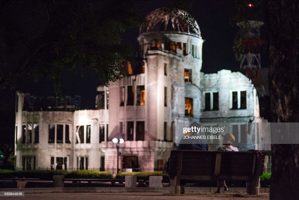 A couple sits on a bench in front of the Hiroshima Peace Memorial Genbaku Dome in Naka Ward, Hiroshima Prefecture on May 24, 2016. US President Barack Obama is scheduled to make a historic visit to the atomic-bombed city on May 27. / AFP / JOHANNES