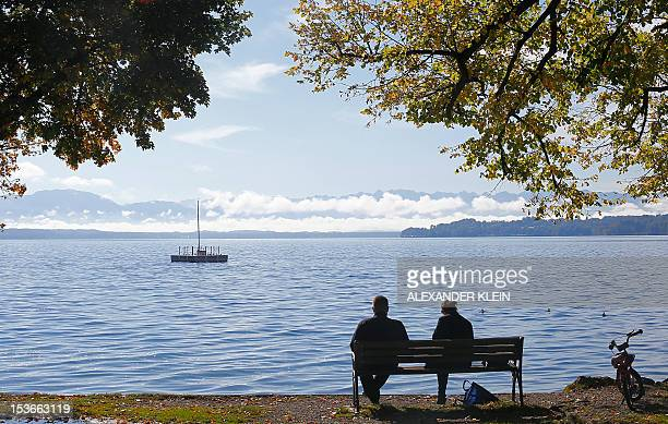A couple sits on a bench in front of the Starnberger See lake in Tutzing near Starnberg some 20km south west of Munich on October 8 2012 AFP PHOTO /...