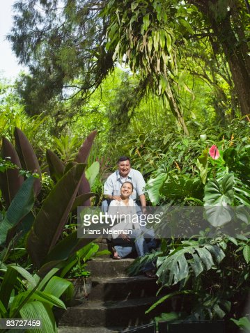 Couple sits on steps in lush garden