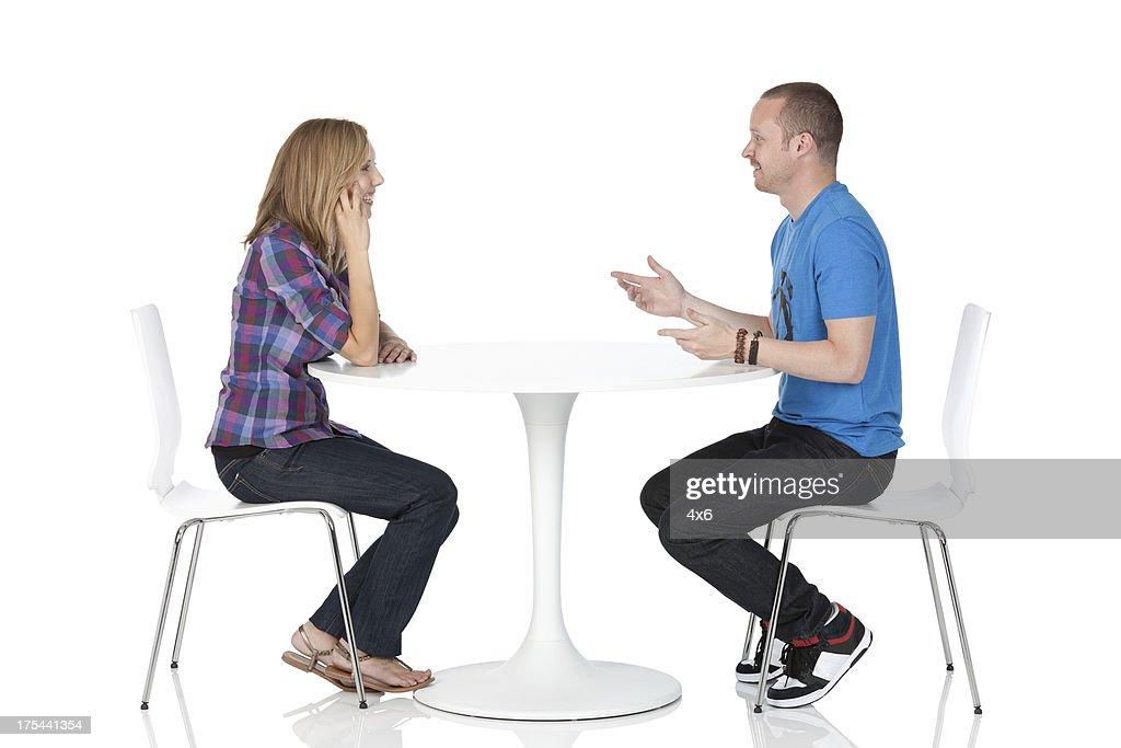Paar sitzt auf einer anderen auf einem Tisch : Stock-Foto