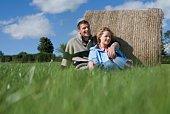 Couple sitting against hay bale in rural Ireland