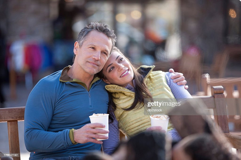 Couple sitting and enjoying warm drinks outside : Stock Photo