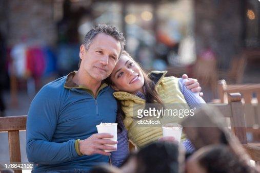 Couple sitting and enjoying warm drinks outside : Stock Photo