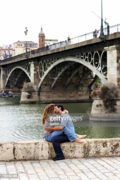 Couple sitting and kissing by bridge, side view,Guadalquivir River, Seville, Spain