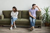 Husband and wife sitting on different sides of couch not looking at each other and not talking, being in quarrel thinking about relationship problems, break up. Concept of family misunderstanding