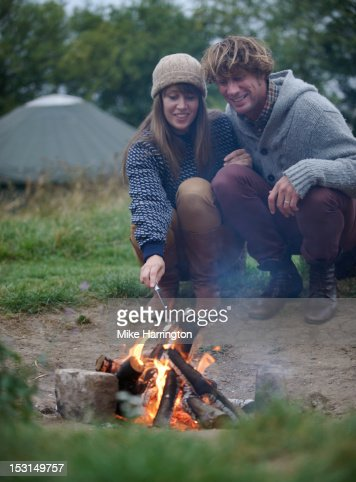 Couple sitting around fire toasting marshmallows. : Stock Photo