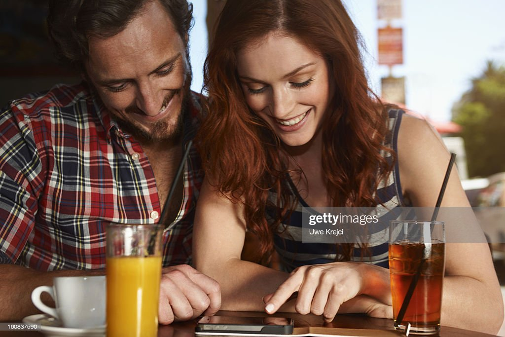 Couple sitting at a restaurant table, close up : Stock Photo
