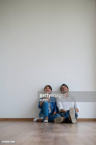 Couple assis devant une salle vide, parler de design d'intérieur