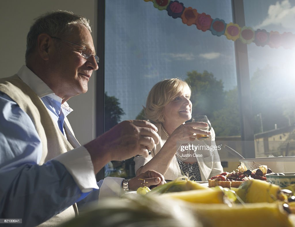 Couple sitting at buffet table : Stock Photo
