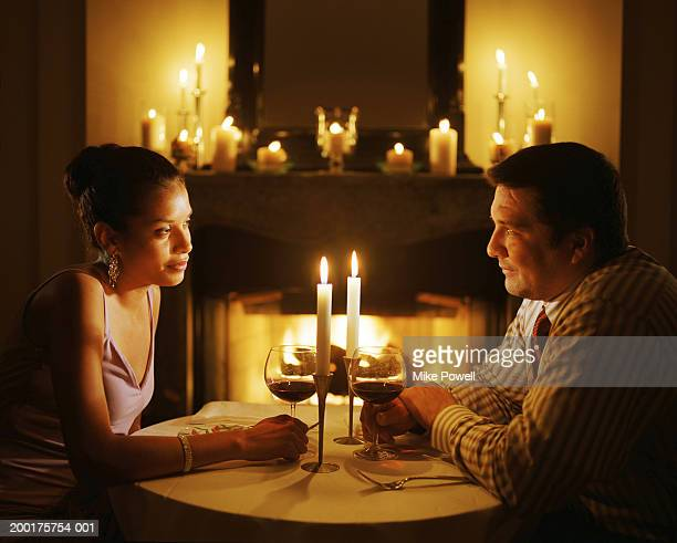 Couple sitting at candle lit table next to fire