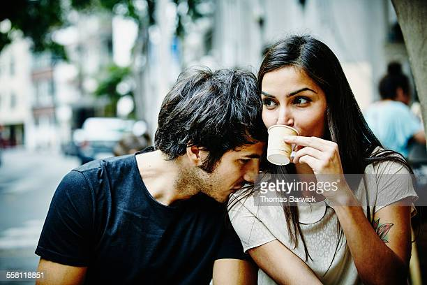Couple sitting at city cafe drinking espresso