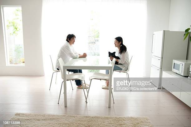 Couple sitting at dining table with Chihuahua