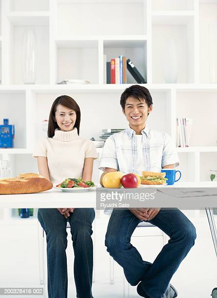 Couple sitting at dinning table, smiling