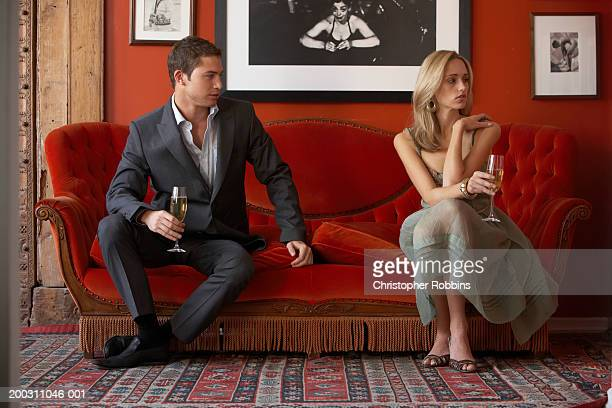 Couple sitting at opposite ends of sofa