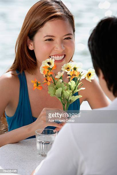 Couple sitting at outdoor cafe, woman holding flowers