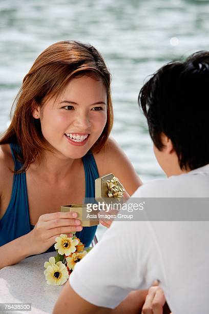 Couple sitting at outdoor cafe, woman opening gift box, smiling at man