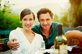 Couple sitting at outdoor meal table in yard
