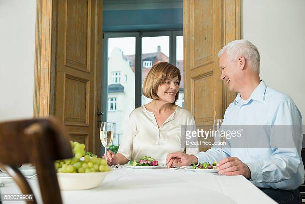 Couple sitting at table and looking at each other, smiling