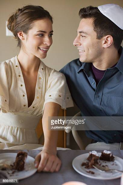 Couple sitting at table in front of slice of cake