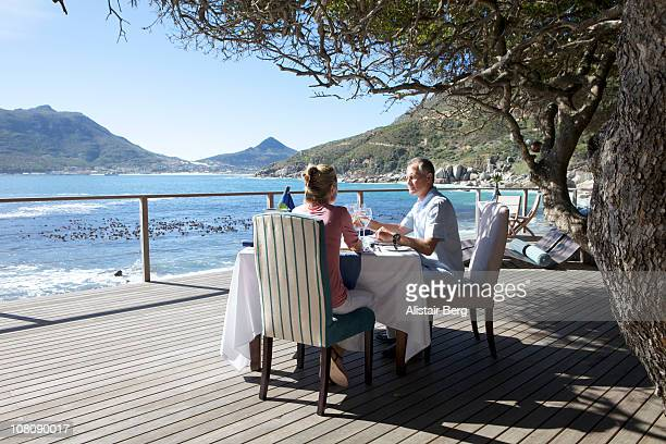 Couple sitting at table overlooking sea