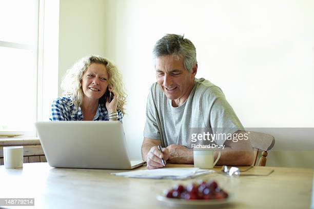 Couple sitting at table using laptop and phone