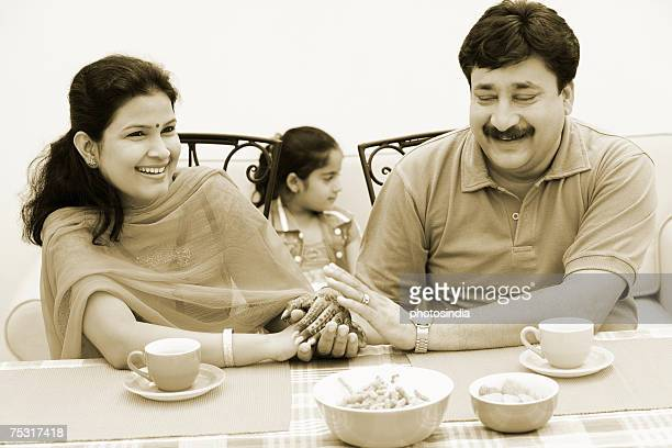 Couple sitting at the dining table and holding hands with their daughter sitting behind them