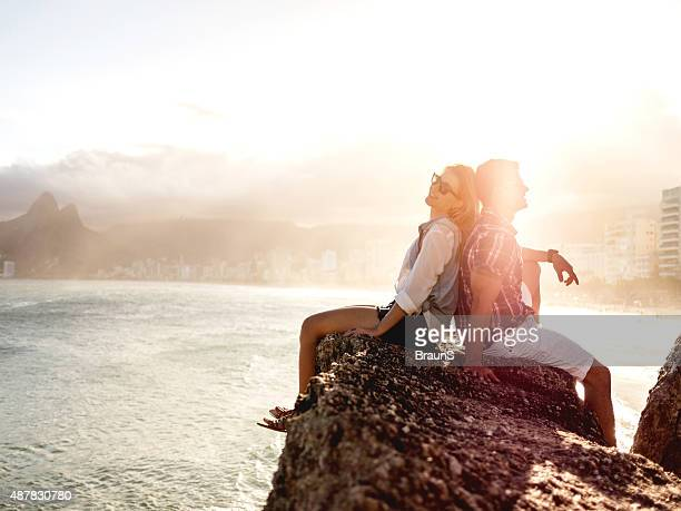 Couple sitting back to back on a rock at sunset.
