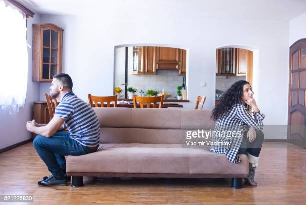 Couple sitting back to back on sofa at home