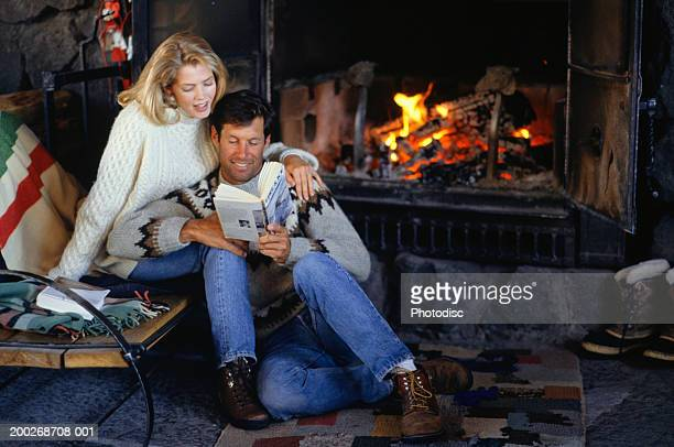 Couple sitting by fireplace, reading book